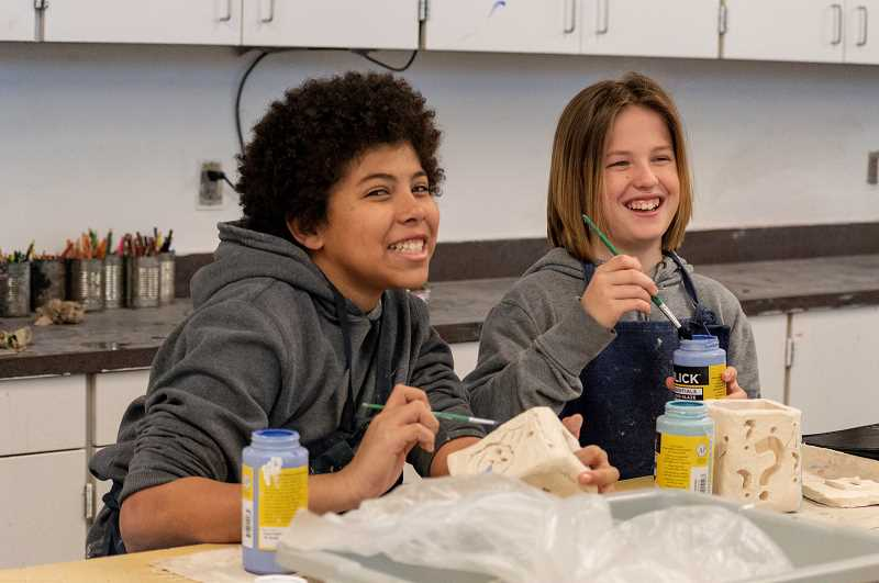 SPOKESMAN PHOTO: CLARA HOWELL  - Seventh-graders JonMarc Stevens, left, and Grayson Atwood decorate their clay lanterns for Portland's Winter Light Festival.