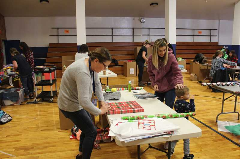 KRISTEN WOHLERS - Ninety-One parents wrap gifts for fellow school families on Monday, Dec. 10.