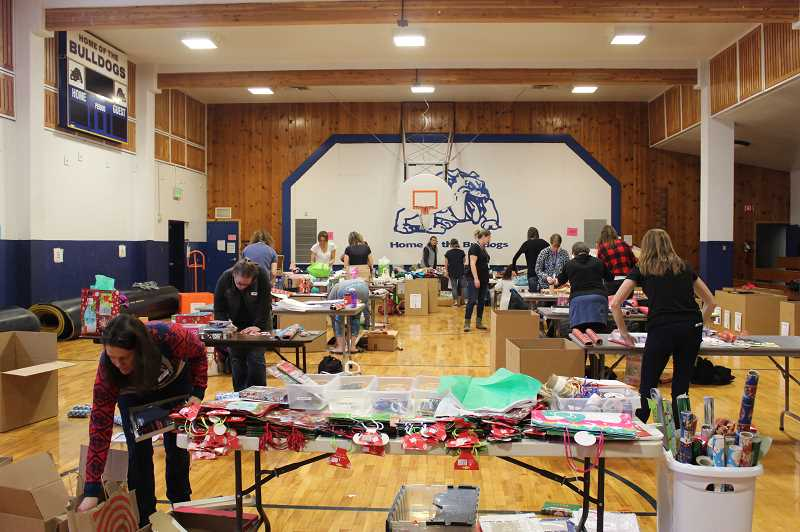 KRISTEN WOHLERS - Participating parents are busy at work, wrapping gifts for families.