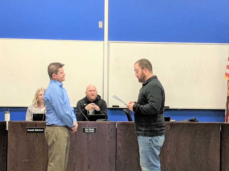 ESTACADA NEWS PHOTO: EMILY LINDSTRAND - Estacada School Board Chair Ben Wheeler leads recently appointed director Will Johnston in the oath of office during a meeting on Wednesday, Dec. 12