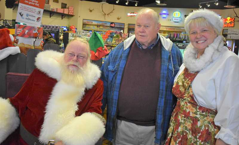 ESTACADA NEWS PHOTO: EMILY LINDSTRAND - Barton Christmas Corner organizer Don Burton smiles with Santa and Mrs. Claus during a new holiday event in Barton last weekend.