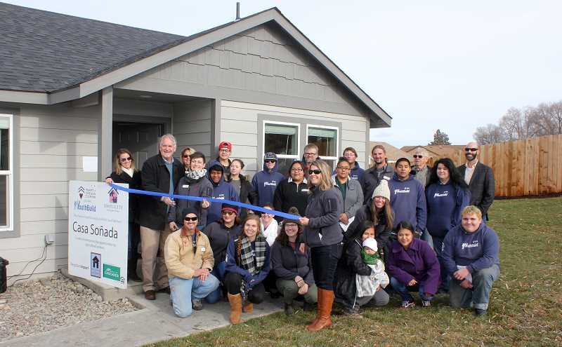 SUSAN MATHENY/MADRAS PIONEER - Housing Works Director David Brandt cuts the ribbon on house No. 6 in Madras, surrounded by YouthBuild crew members and partners.