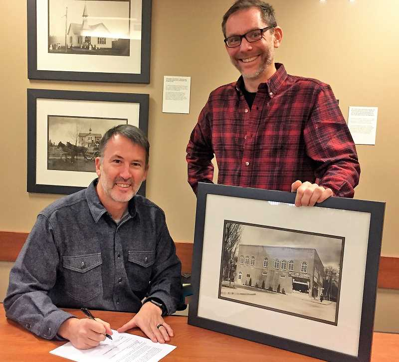 SUBMITTED PHOTO: SIOBHAN TAYLOR - WFHAC President Jon Gustafson, left, signs the letter of intent next to West Linn Community Development Director John Williams. The picture held by Williams depicts the building in its orginal state, as a grocery store combined with city hall.