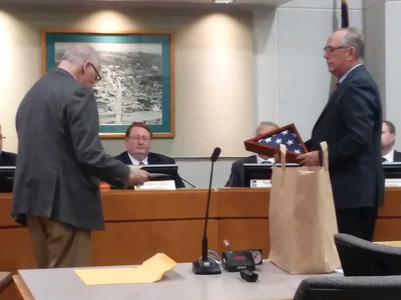 TIMES PHOTO: RAY PITZ - Forest Grove Mayor Pete Truax, left, and Hillsboro Mayor Steve Callaway present Tigard Mayor John Cook with a flag that once flew over the U.S. Capitol.