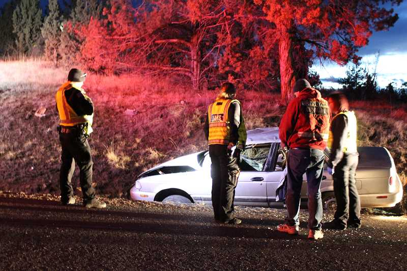 HOLLY M. GILL/MADRAS PIONEER - Emergency crews survey a 1994 Nissan Sentra in a ditch on the side of Northeast Loucks Road on Friday, Dec. 14. The 21-year-old driver, who left the scene, was later arrested on a warrant.