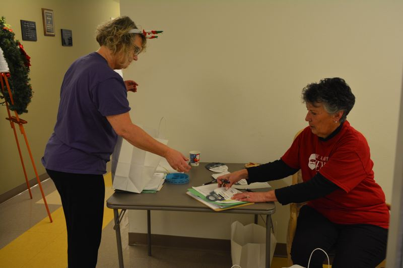 SPOTLIGHT PHOTO: COURTNEY VAUGHN - Phyllis Peabody and Dianne Juergens, employees with Home Instead Senior Care, check off names on a list of seniors slated to receive a gift delivery just in time for the holidays.