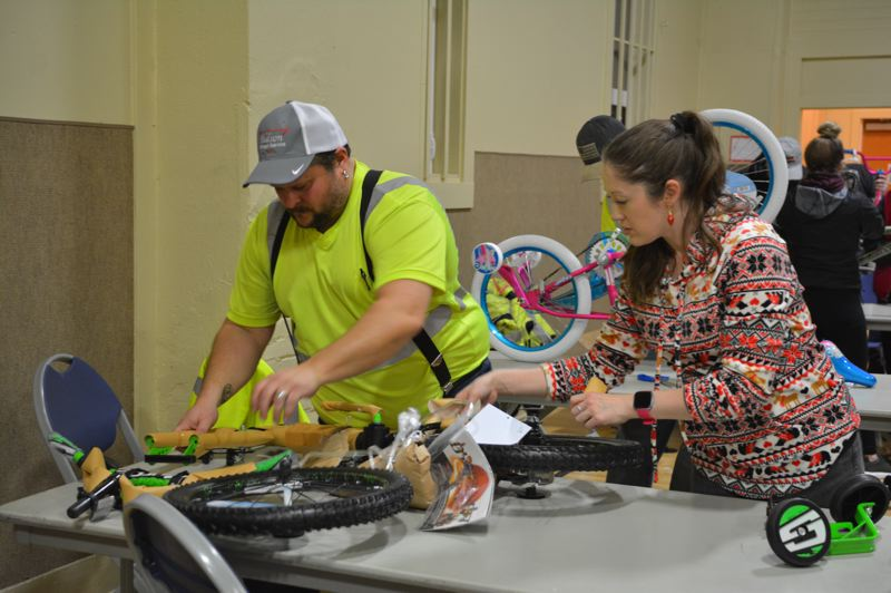 SPOTLIGHT PHOTO: COURTNEY VAUGHN - Larry Maccarone and Kimberly Frakes of Hudson Garbage work together to assemble childrens bikes during a build-a-bike event in Columbia City. Volunteers worked to assemble more than 130 bikes for children Friday, Dec. 14.
