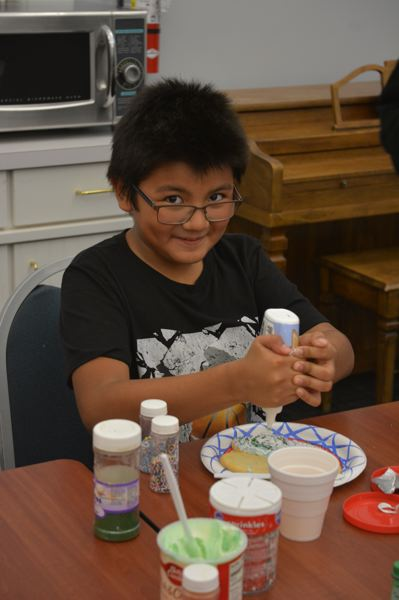 SPOTLIGHT PHOTO: COURTNEY VAUGHN  - Moises Vasquez, 10, puts the finishing touches on a sugar cookie Friday, Dec. 14, at the Scappoose Public Library. The free cookie decorating session featured festive frosting and sprinkles for kids in grades six through 12.