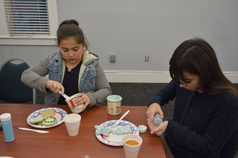 SPOTLIGHT PHOTO: COURTNEY VAUGHN  - Matika, 10 and Althea Pisha, 12, pick out sweet decorations for Christmas cookies at the Scappoose library. Tweens and teens were invited to come decorate cookies and enjoy the fruits of their labor.