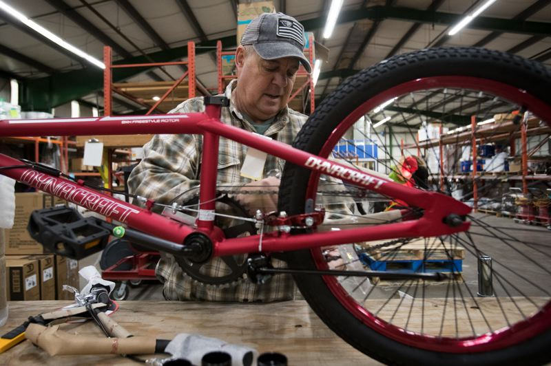 PAMPLIN MEDIA GROUP: JAIME VALDEZ - Mike Crawford, owner of Pioneer Waterproofing in Tigard, builds a youth bike in the warehouse of his business. Crawford along with his family and employees of the company, assembled bikes to be donated for an annual toy drive coordinated by local television station KGW.