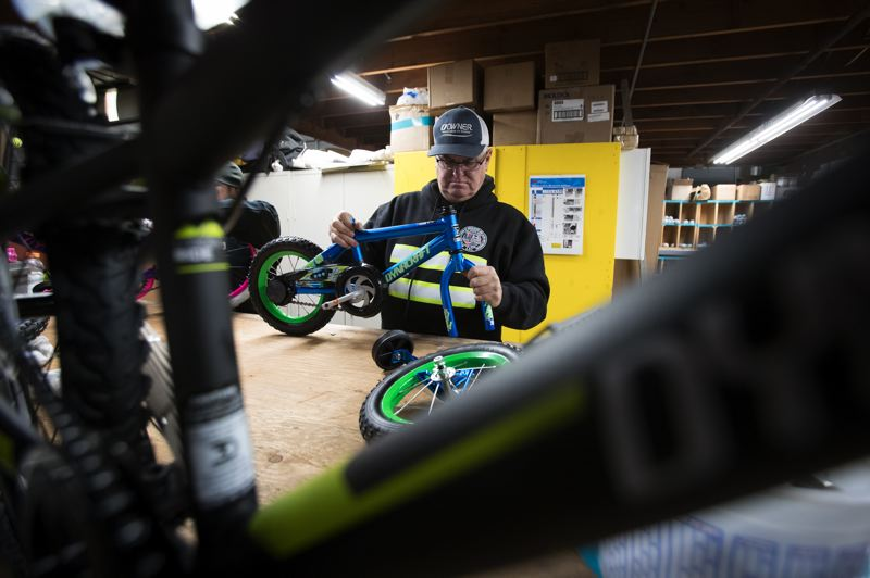PAMPLIN MEDIA GROUP: JAIME VALDEZ - Randy McAdams, a former employee of Pioneer Waterproofing for 20 years, builds a youth bike in the warehouse of the Tigard business. McAdams who now sells parts to his former company, continues to volunteer to build bikes because its his favorite way to give back.