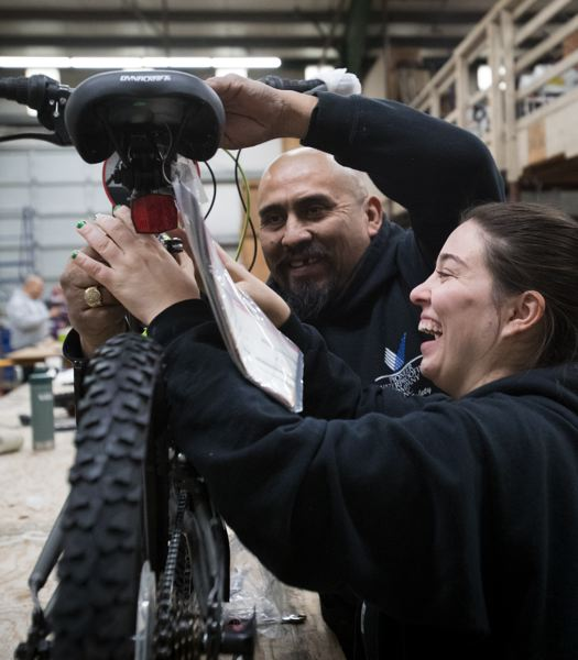 PAMPLIN MEDIA GROUP: JAIME VALDEZ - Noe Alonso, an employee with Pioneer Waterproofing, helps Katey Crawford build a youth bike in the warehouse of the Tigard company. Katey's dad, Mike Crawford, owns the business.