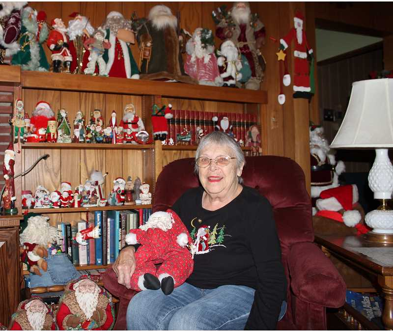 HOLLY SCHOLZ/CENTRAL OREGONIAN  - Norma Jones sits amidst part of her Santa Claus collection. Each December, she displays hundreds of Santa dolls and figurines in her living room.