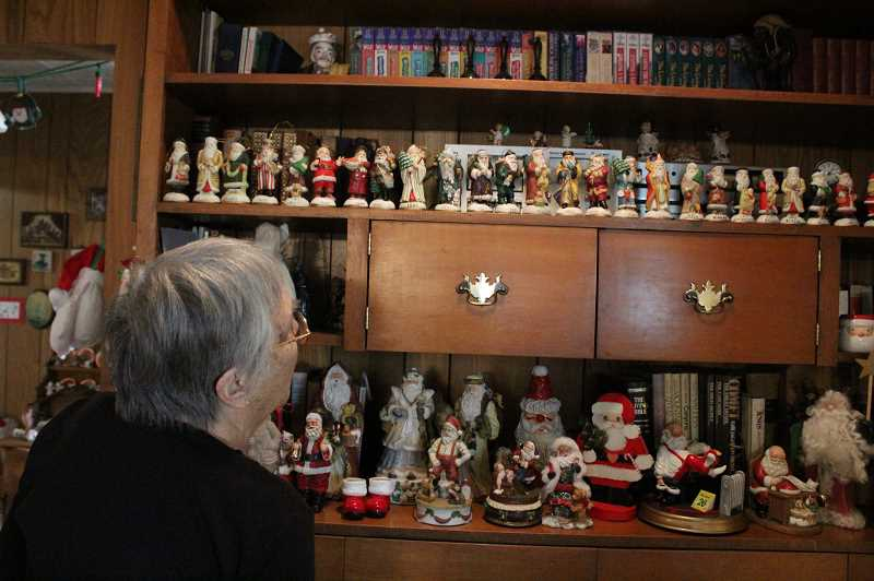 HOLLY SCHOLZ/CENTRAL OREGONIAN  - Norma Jones looks over part of her massive collection of Santas she has accumulated through the years.