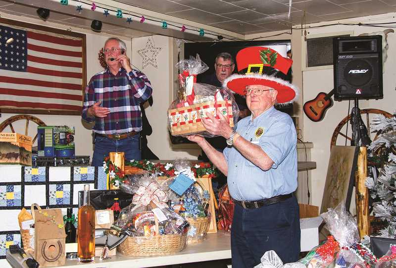 PHOTO COURTESY OF MICHAEL REDHEAD  - American Legion Commander Bob Huntington, wearing the Christmas hat, holds up a gift basket while auctioneer Dennis Helms, left, gets bids during the Dec. 14 holiday auction.