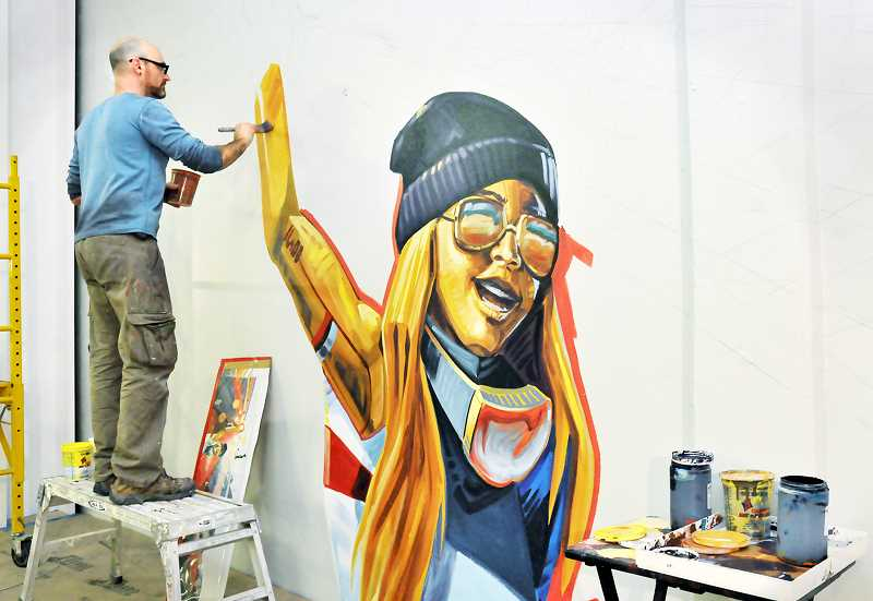 GARY ALLEN - Dan Cohen continues work on a giant mural that will cover three walls adjacent to the elevated running track at the fitness center.