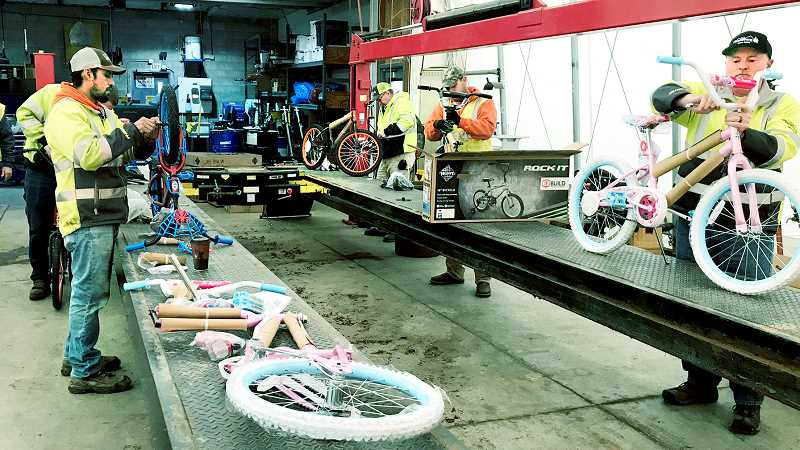 SUBMITTED PHOTO - City of Newberg public works employees assemble bicycles to be given out during the Toy & Joy effort.