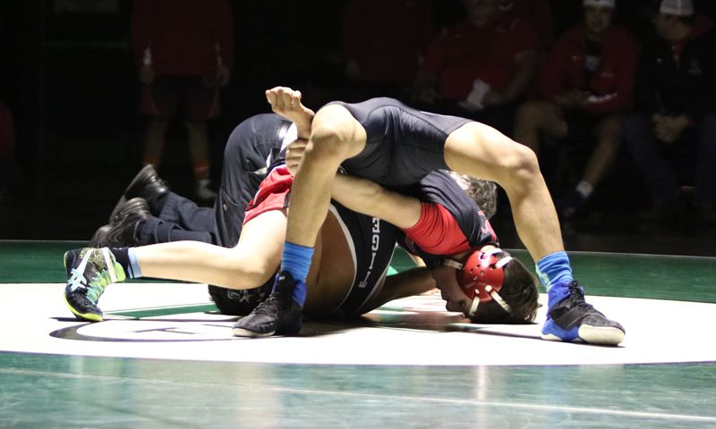 PAMPLIN MEDIA: JIM BESEDA - Oregon City's Chris Tyler presses his forehead to the mat as he pins Tigard's Cruz Hernandez at 2:46 in the 120-pound match at Thursday's Three Rivers League wrestling dual at Tigard High.