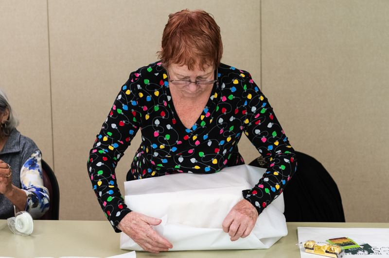 STAFF PHOTO: CHRISTOPHER OERTELL - Mary Brottlower uses tissue paper to wrap a gift during the Forest Grove wrapping party on Tuesday, Dec. 18.