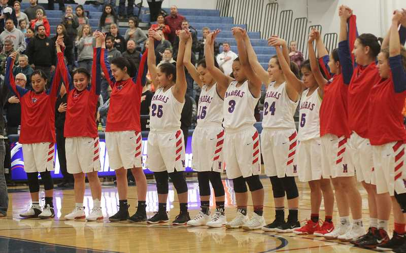 WILL DENNER - The Madras White Buffalo girls basketball team, led by Lynden Harry raises their arms together at a game last season. Harry earned Tri-Valley Conference Player of the Year for the third year in a row in spring 2018.