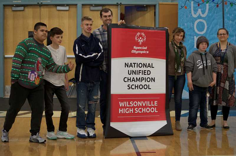 SPOKESMAN PHOTO: CLARA HOWELL  - Jean Hansen, vice president of School Partnerships and Youth Outreach with Special Olympics Oregon, presents WHS with the National Unified Champion School banner.
