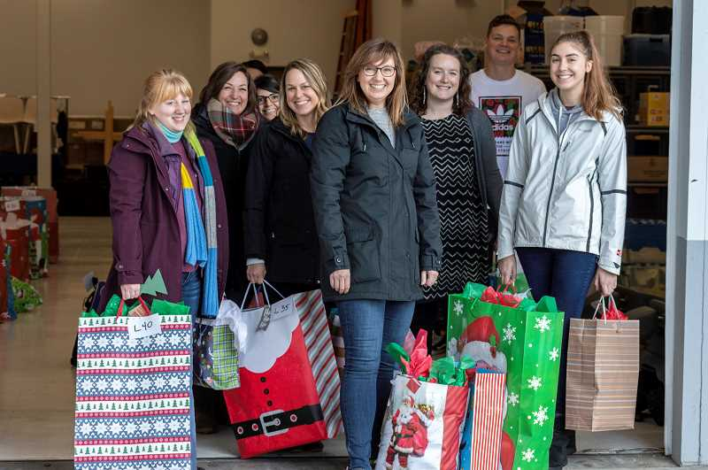 SPOKESMAN PHOTO: CLARA HOWELL  - From left to right: Grace Chapel staff Courtney Carter, Brittany Turco, Uma Eichlet, Amy Shank, Jen McCourt, Amanda Rogers, Dylan Erickson and Emma Weaver get ready to deliver holiday gifts to Wilsonville schools.