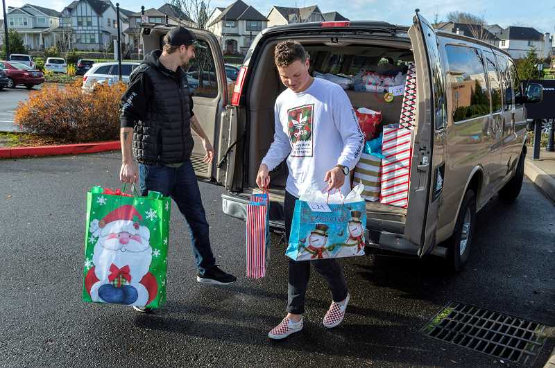 SPOKESMAN PHOTO: CLARA HOWELL - Austin Nealeigh, left, and Dylan Erickson unload gifts to deliver to Lowrie Primary.