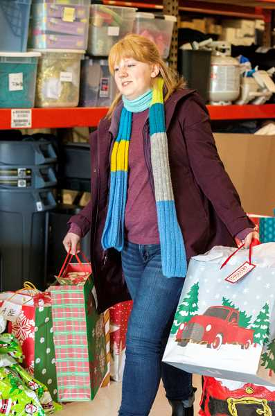 SPOKESMAN PHOTO: CLARA HOWELL  - Courtney Carter helps load the holiday gifts into cars before she helps deliver them to Wilsonville schools.