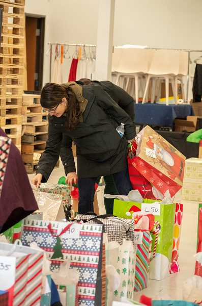 SPOKESMAN PHOTO: CLARA HOWELL - Uma Eichlet helps carry the gifts to the cars so staff can deliver the presents.