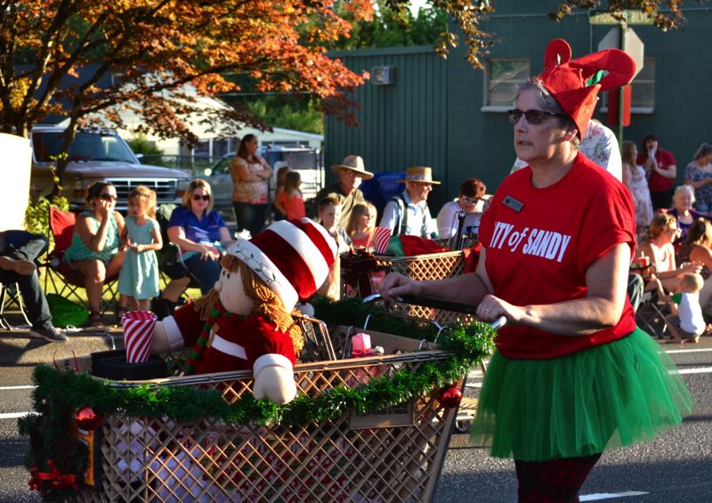 POST PHOTO: BRITTANY ALLEN - In the spirit of Sandy Mountain Festival's 2017 'Christmas in July' theme, City Manager Kim Yamashita dressed up as an elf and pushed a shopping cart to promote the Shop with a Cop program.