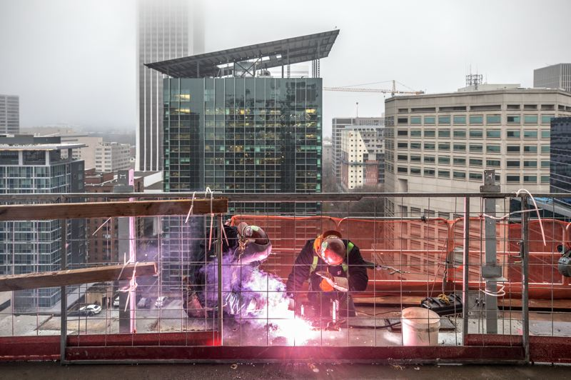 TRIBUNE PHOTO: JONATHAN HOUSE - Tellis Symonette, left, and Jessy Gonzalez weld plates on an upper story of the new Multnomah County Central Courthouse building.