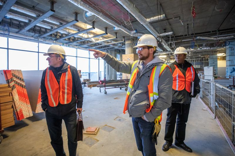 TRIBUNE PHOTO: JONATHAN HOUSE - Justin Paterson, center, project manager for Hoffman Contstruction, points out the location of a jury waiting room during a project tour with Multnomah County spokesman Mike Pullen, left, and Multnomah County supplier diversity officer Lee Fleming.