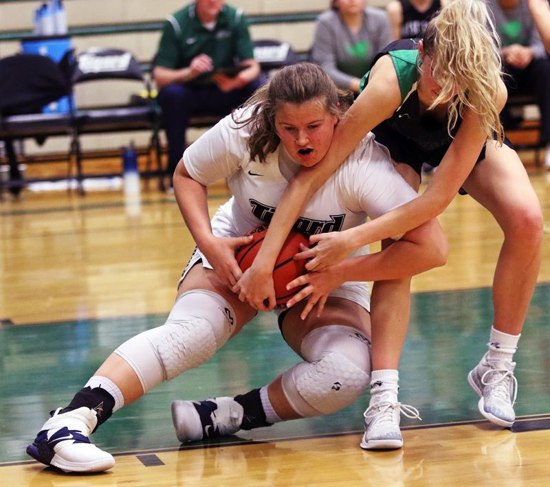 TIMES PHOTO: DAN BROOD - Tigard senior post Dani Lyons (left) battles West Salem senior Maddie Bertsch for the ball during Fridays contest. The Tigers came away with a 64-57 win.