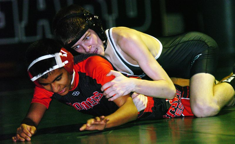 TIMES PHOTO: DAN BROOD - Tigard High School freshman Atticus Waddell takes control in his 106-pound bout against Oregon Citys Oscar Cuellar. Waddell won by fall in 3:14.