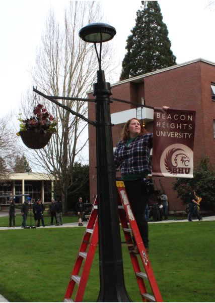 STAFF PHOTO: OLIVIA SINGER - The banner of fictional Beacon Heights University is installed on a lamppost at Pacific University during filming for a television pilot in March.