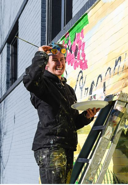STAFF PHOTO: OLIVIA SINGER - Artist Holly Henderson of Beaverton paints a mural for Travel Oregon in downtown Forest Grove in November.