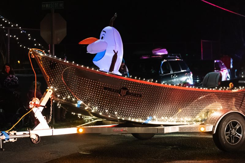 STAFF PHOTO: CHRISTOPHER OERTELL - An inflatable Olaf the snowman rides in a boat being towed in the annual Jingle Thru North Plains holiday parade on Dec. 6.
