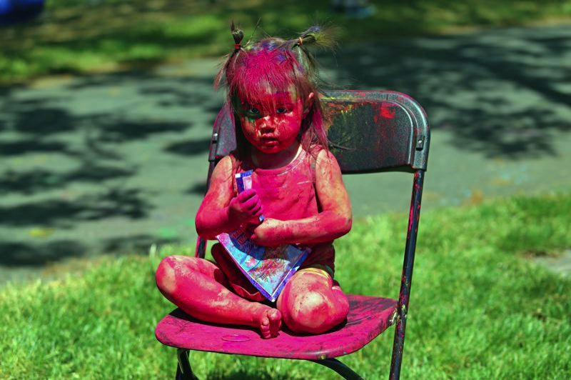 TIMES PHOTO: JESSICA DARLAND - Greta Franck, 2, of Portland takes the Indian Festival of Color very, very seriously during the May Rang Barse celebration in Hillsboro.