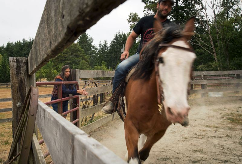 TIMES PHOTO: JAIME VALDEZ - Kathryn Kleinwatcher keeps an eye on her son, Travis Groth, as he rides Diesel at her home in Port Orchard, Wash. Diesel previously served in the Portland Police Mounted Patrol Unit.