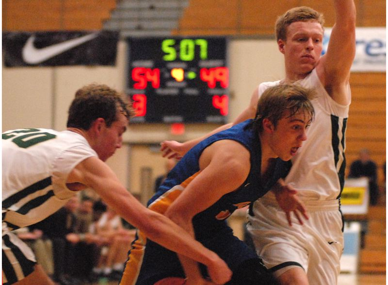 OUTLOOK PHOTO: DAVID BALL - Barlows Noah Lowery tries to split a pair of defenders on a drive to the basket in the fourth quarter of the Bruins 63-59 loss to Jesuit on Wednesday.