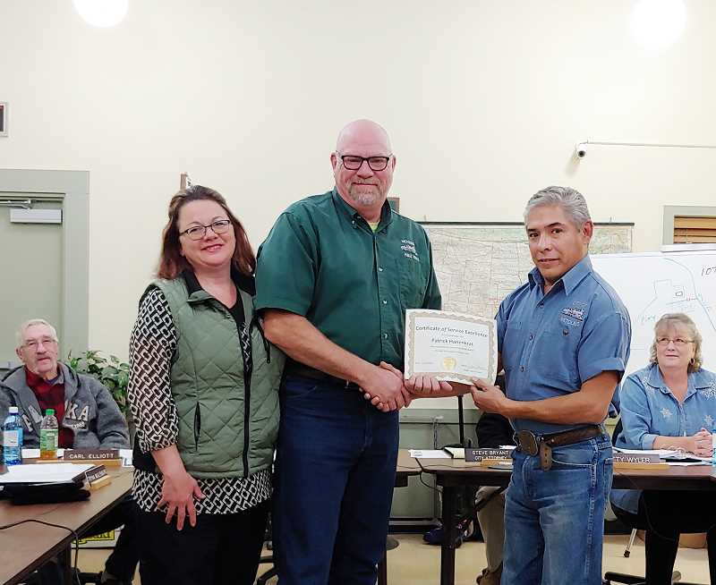 SUBMITTED PHOTO - Pat Hanenkrat, center, with his wife, Kimberly, accepts an award from Metolius Mayor John Chavez.