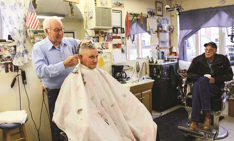 HOLLY SCHOLZ/CENTRAL OREGONIAN   - Barber Monte Gibson gives a haircut to John Harrison while visiting with John Nelson. A lot of guys come into the barbershop just to visit.