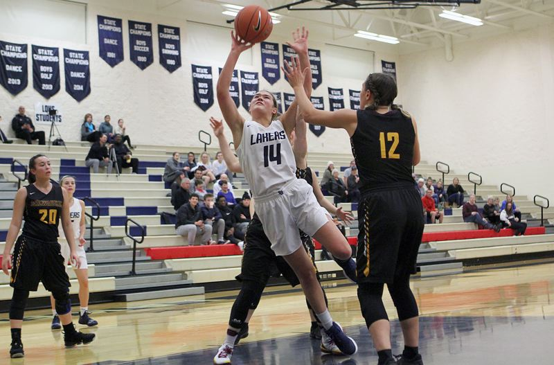 REVIEW PHOTO: MILES VANCE - Lake Oswego sophomore Macy Douglass squeezes through the Milwaukie defense to score during her team's 63-44 win in the first round of the Nike Interstate Shootout on Dec. 26 at Lake Oswego High School.