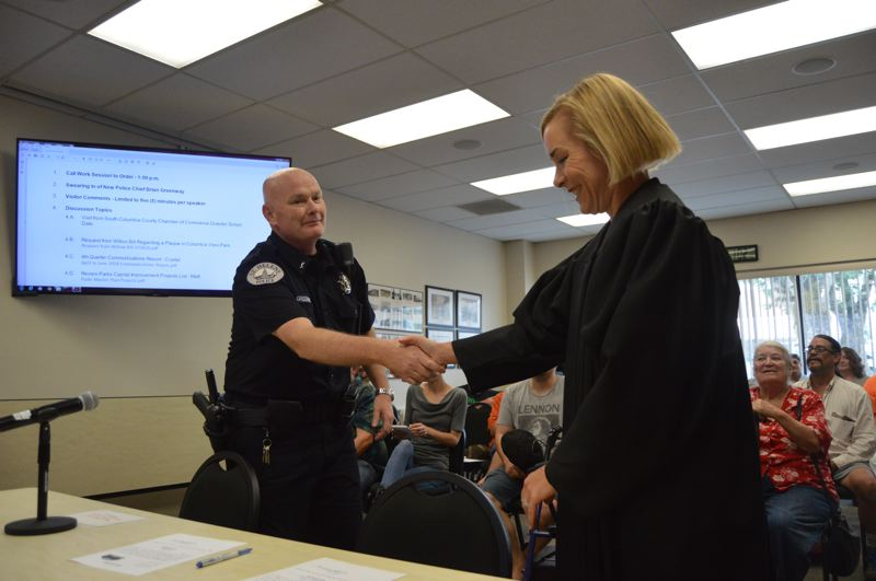 SPOTLIGHT FILE PHOTO - St. Helens Police Chief Brian Greenway, left, shakes the hand of St. Helens Municipal Court Judge Amy Lindgren after being sworn in as the new police chief in August.