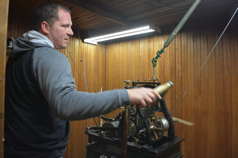 SPOTLIGHT PHOTO: COURTNEY VAUGHN - Andy Ventris, a Columbia County facilites employee, cranks a lever to wind the historic Columbia County Courthouse clock. The clock, which is now more than 100 years old, requires constant winding and maintenance to keep it running.