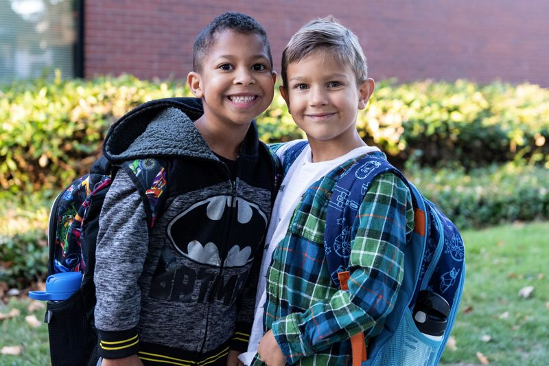 STAFF PHOTO: CHRISTOPHER OERTELL - Best friends Anakin Murray and Finn Rumore pose for a photo before beginning first grade on the first day of school at Orenco Elementary School this September.
