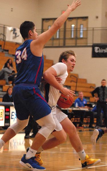 OUTLOOK PHOTO: DAVID BALL - Barlows Jaren Hunter looks to drive past Churchill center Dylan Carson during the second half.
