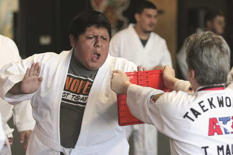 PHIL HAWKINS - Miguel Martinez prepares to strike a breaking board held by Tawnia Mauro at the ATA Martial Arts & Karate for Kids dojo in Keizer.