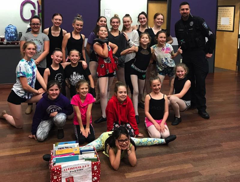 Oregon City Sgt. Dave Edwins accepts a donation of new books from Grand Finale Dance Studio in Gladstone for the OCPD Christmas 911 benefit.