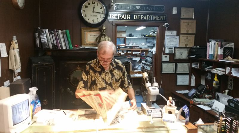 PHOTO BY RAYMOND RENDLEMAN - Store owner Gary Ruud looks over memorabilia in the business that's been open for more than 50 years in downtown Oregon City.